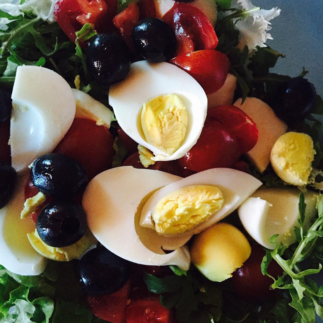 Insalata con uova di quaglia, rughetta, pomodori e olive.